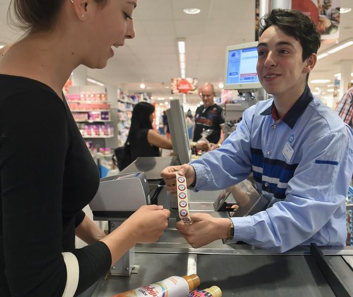 Kassamedewerker Levy Geernaert van AH overhandigt de spaarzegels.