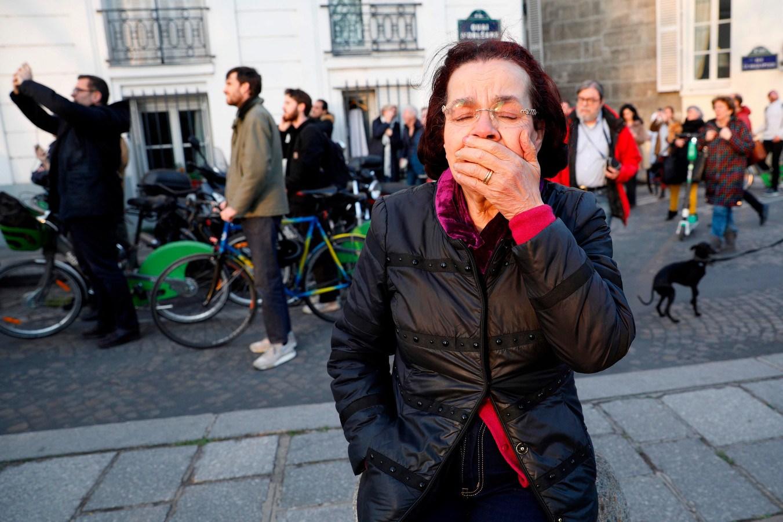 Een vrouw kijkt toe hoe de vlammen uit de Notre-Dame slaan
