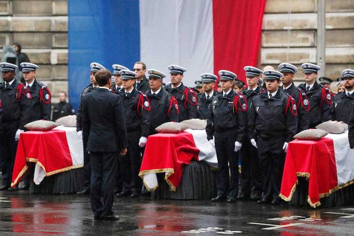De Franse president Emmanuel Macron bewijst de doodgestoken agenten de laatste eer.