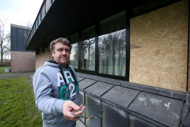 Ronny Bulcke, verantwoordelijke van crematorium De Blauwe Toren,met een glasscherf. De kapotgeslagen ruit achter hem werd intussen tijdelijk gedicht.