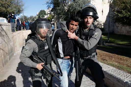 Een Palestijnse jongeman wordt weggevoerd door de Israëlische grenspolitie.