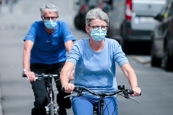 Fietsers met een mondmasker. Dit is een illustratiebeeld.