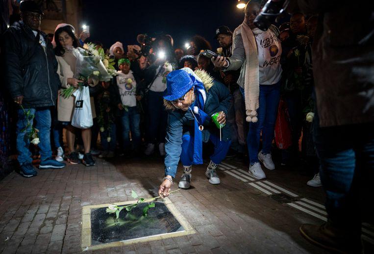 De moeder van Rapper Bolle (met blauwe hoed) legt donderdag bloemen bij de gedenksteen van haar zoon tijdens de herdenking in Amsterdam-Zuidoost. Rapper Bolle werd een jaar geleden vermoord.  Beeld Foto Freek van den Bergh / de Volkskrant