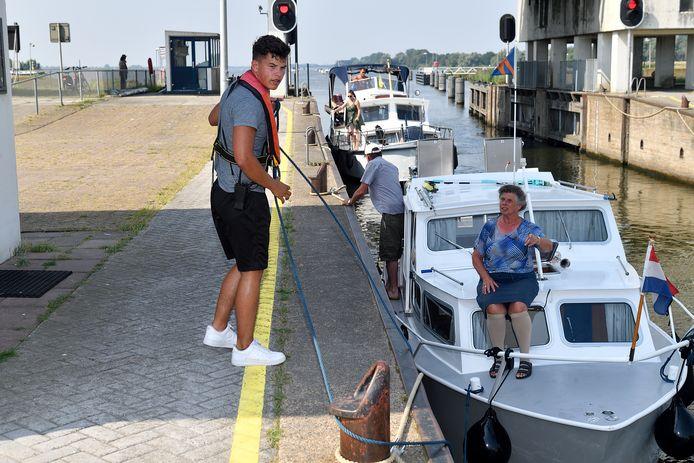 Sluissteward Jilles Kok assisteert schippers met het aanleggen van hun bootje.
