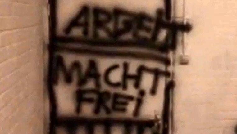 Beeld uit het Minerva-huis: op een muur staat de tekst 'Arbeit macht frei' Beeld Volkskrant