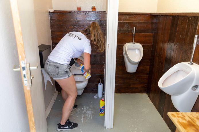 De toiletjuffrouw van strandtent Beach maakt constant de toiletten schoon.