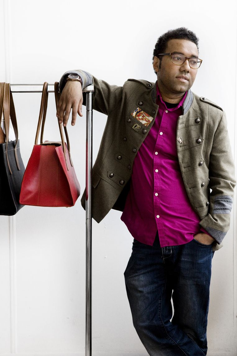 Tassenmaker Omar Munie met twee van zijn ontwerpen. Beeld Io Cooman