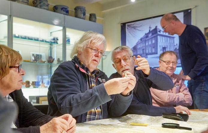 In het oude raadhuis te Erp is steentijd-deskundige Pieter Dijkstra (middenlinks) oude vondsten aan 't determineren.