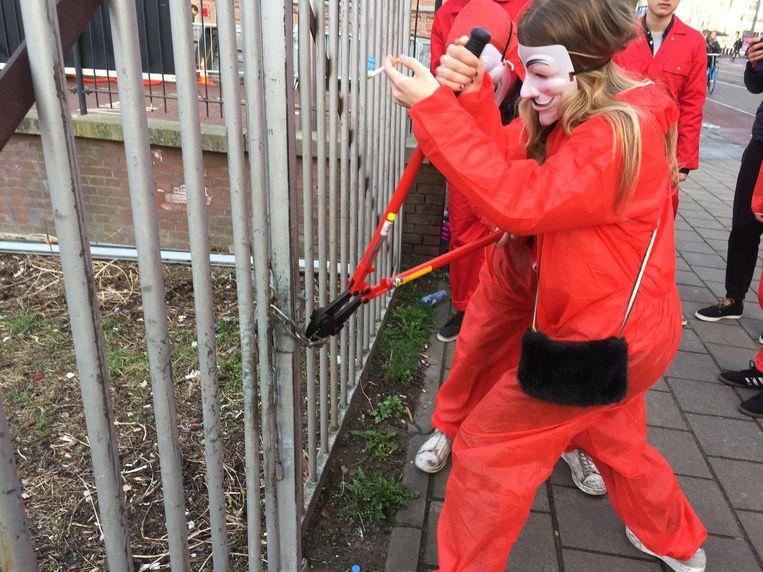 Stiekem zijn de eindexamenleerlingen van het Barlaeus door het hek gekomen, nadat ze het slot hadden doorgknipt. Beeld Lorianne van Gelder