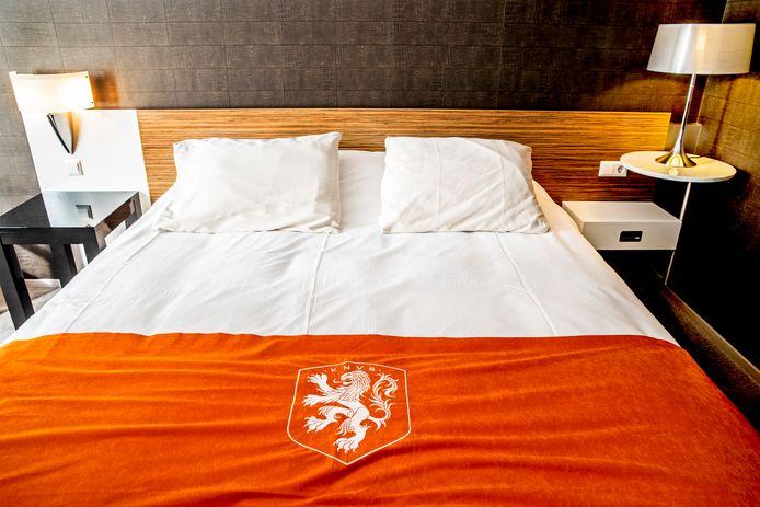 De slaapkamer van de internationals met oranje sprei.