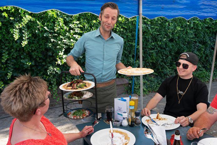 Victor van Loon serveert een aantal pannenkoeken op het extra terras van Pannenkoekengoed.