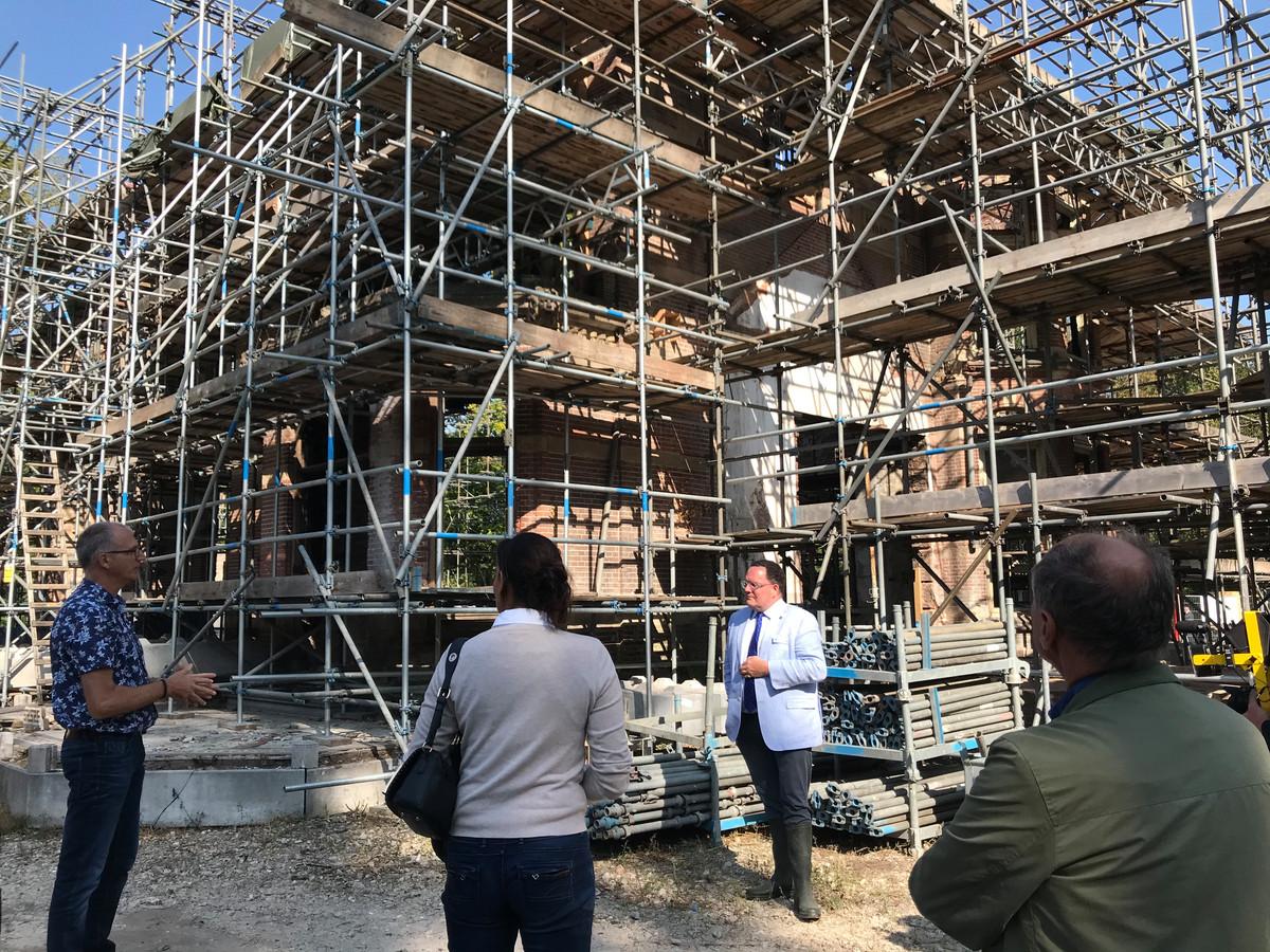 Burgemeester Roderick van de Mortel en verschillende gemeenteraadsleden luisteren tijdens een rondleiding naar de plannen met Zionsburg.