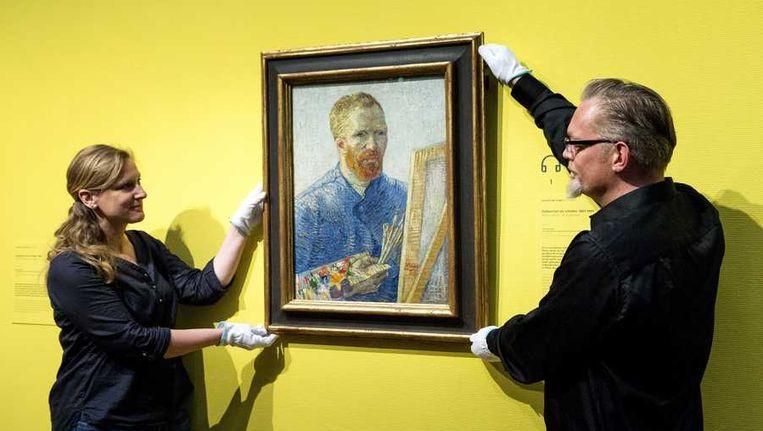 Medewerkers van het Van Gogh Museum hangen voorafgaand aan de heropening een zelfportret van Vincent van Gogh op. Beeld anp
