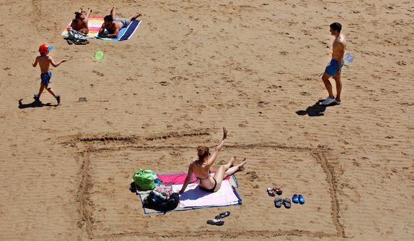 Een vrouw heeft haar stukje strand afgebakend in het zand in Gijon, Asturias, in het noorden van Spanje.