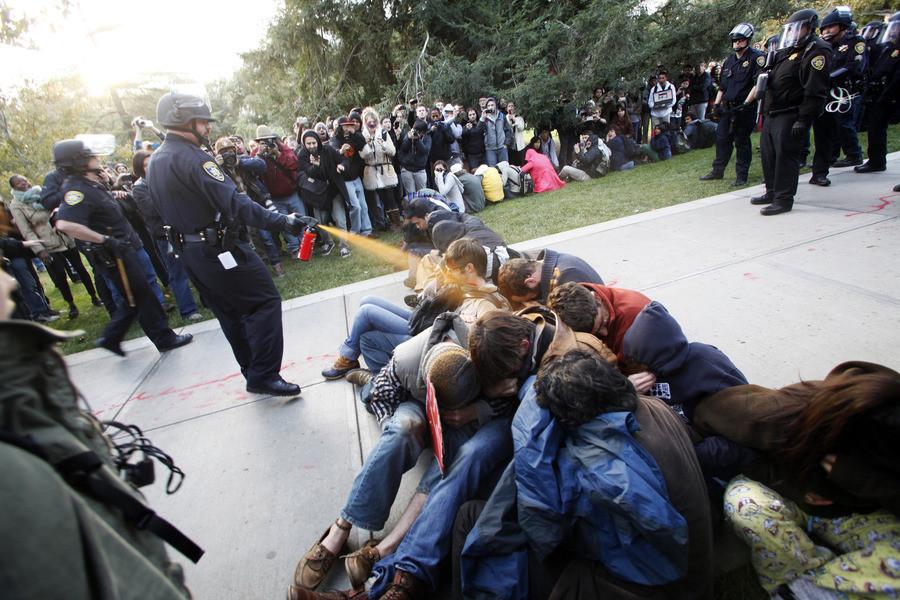 Het politiekorps brak de menselijke ketting van zittende demonstranten op door hen met pepperspray te besproeien.