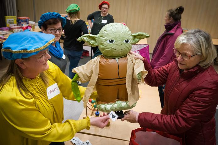 In de Litserborg was een ruilbeurs voor sinterklaas spulletjes. Foto Links vrijwilliger Christel Heijmans die een gremlin uit de film Star Wars  overhandigd krijgt.