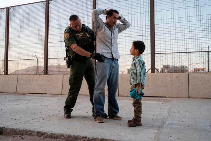 Een Amerikaanse grenswachter in El Paso, Texas fouilleert de 27-jarige José, terwijl zijn zesjarig zoontje José Daniel toekijkt. De man trok een maand lang vanuit Guatemala, via Mexico naar de VS.