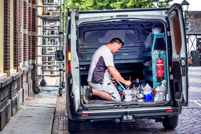 Een schilder/zzp'er aan het werk in zijn busje.  Beeld Raymond Rutting / de Volkskrant