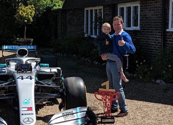 Harry Shaw en vader James voor hun huis naast de F1-bolide van Mercedes.