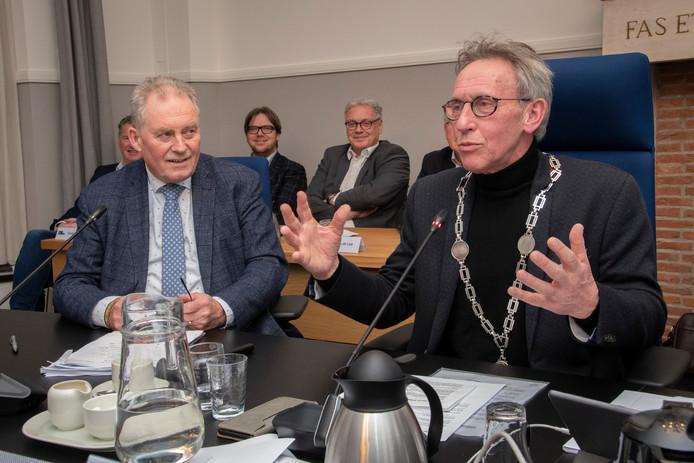 Laatste raadvergadering voor waarnemend burgemeester Harrie Nuijten. Jan van de Wouw (r) heeft zojuist de ambtsketen overgenomen van Harrie Nuijten.