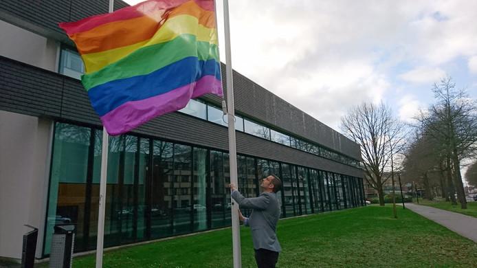 Wethouder Thijs van Kessel hijst de regenboogvlag voor de ingang van het Osse gemeentehuis