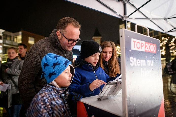 Marice  Drent is aan het stemmen bij de Stembus van de Top 2000, met achter hem zijn vader Patrick en naast hem zijn broertje Ingmar en zus Alicia.