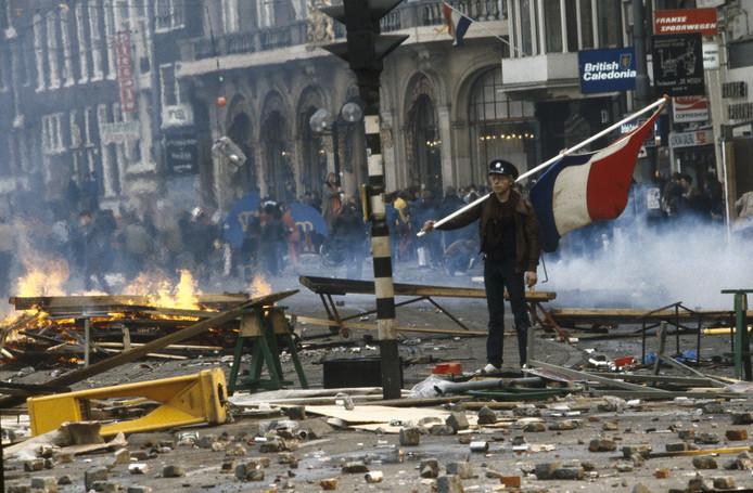 Een kraker staat met een vlag temidden van een enorme ravage op straat tijdens de rellen bij de inhuldiging van koningin Beatrix.