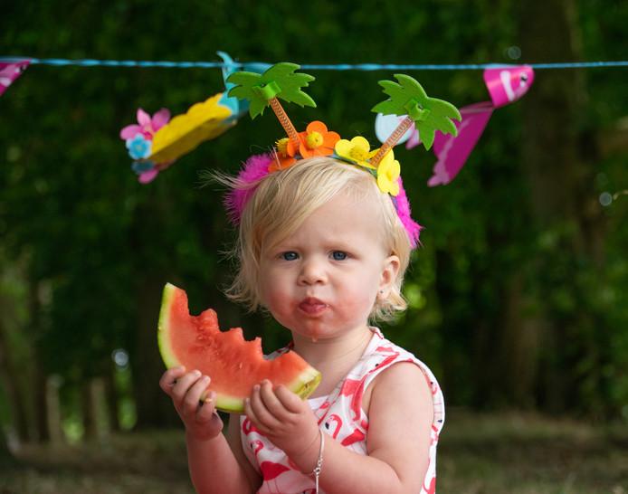 Esmee Ritmeester, 15 maanden oud, eet tijdens de tropische dagen graag een verkoelende watermeloen. Lekker buiten op de stadswal in Gorinchem met een zomers diadeem in haar haar.