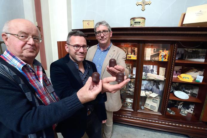 Gidsen van de kapel Piet Peeters, Mark Buys en Pim Wilde met de 'zoen van Buys' en de kast met bakvormen, verpakkingsmateriaal, gadgets en foto's.
