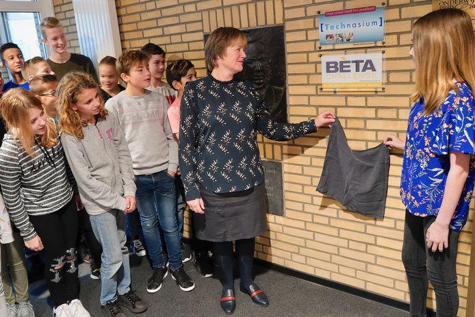 Rector Hanneke Koster onthult, samen met TL-leerlingen, een bordje op de muur.