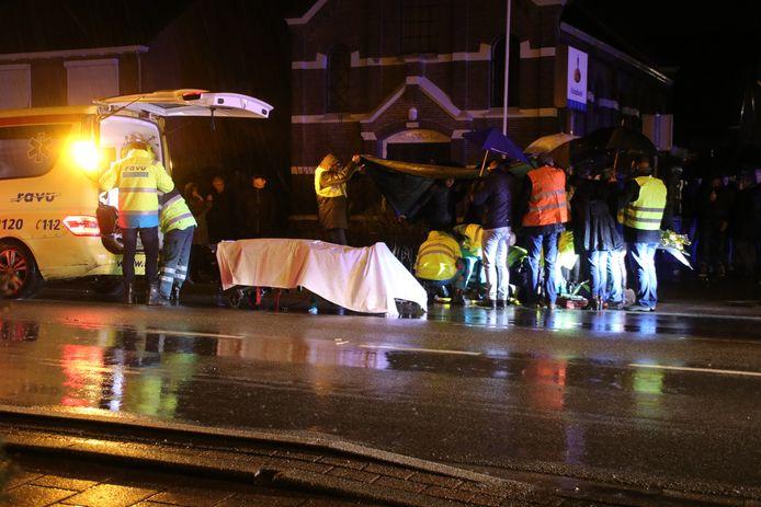 Omstanders proberen met zeil en paraplu's de hulpverleners droog te houden terwijl ze de fietser helpen die in Renswoude door een onbekende automobilist werd geschept. De fietser overleed.