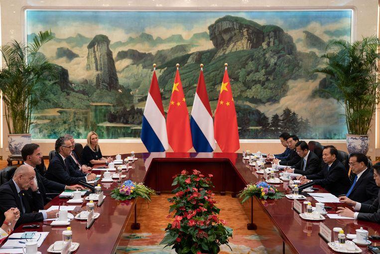 Premier Rutte heeft niet voor niets een oortje in; hij heeft een 'bilateraaltje' met onder meer de Chinese premier Li Keqiang in de Grote Volkshal in Peking. Daar bespreken ze de Nederlandse China-strategie en de handelsoorlog tussen Amerika en China. Morgen vliegt Rutte naar Japan waar hij deelneemt aan de G20. Beeld Getty Images