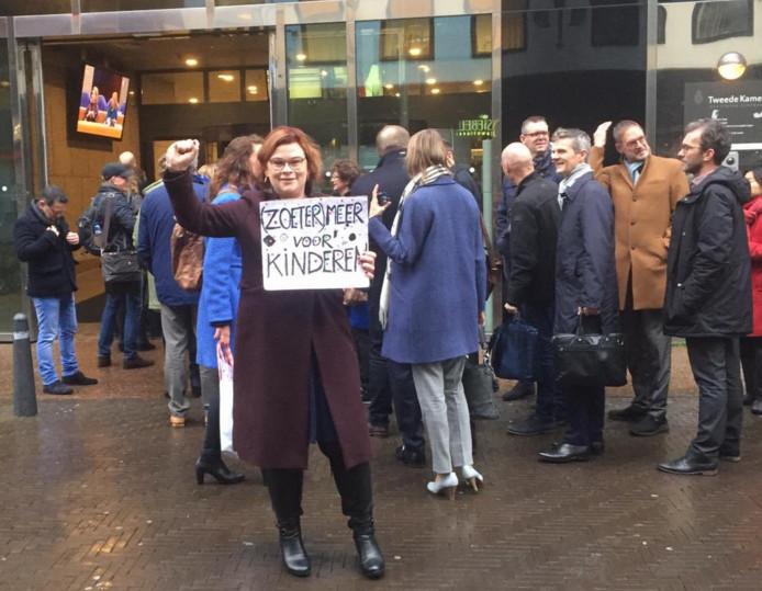Wethouder Jakobien Groeneveld van Zoetermeer met haar protestbord voor de ingang van de Tweede Kamer.