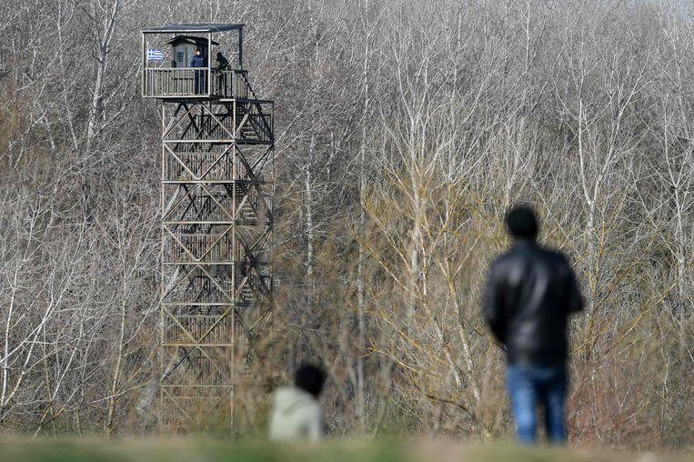 Migranten inspecteren een wachttoren op de Turks-Griekse grens bij Edirne. Beeld AFP