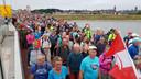 Wandelaars gaan de Waalbrug over.
