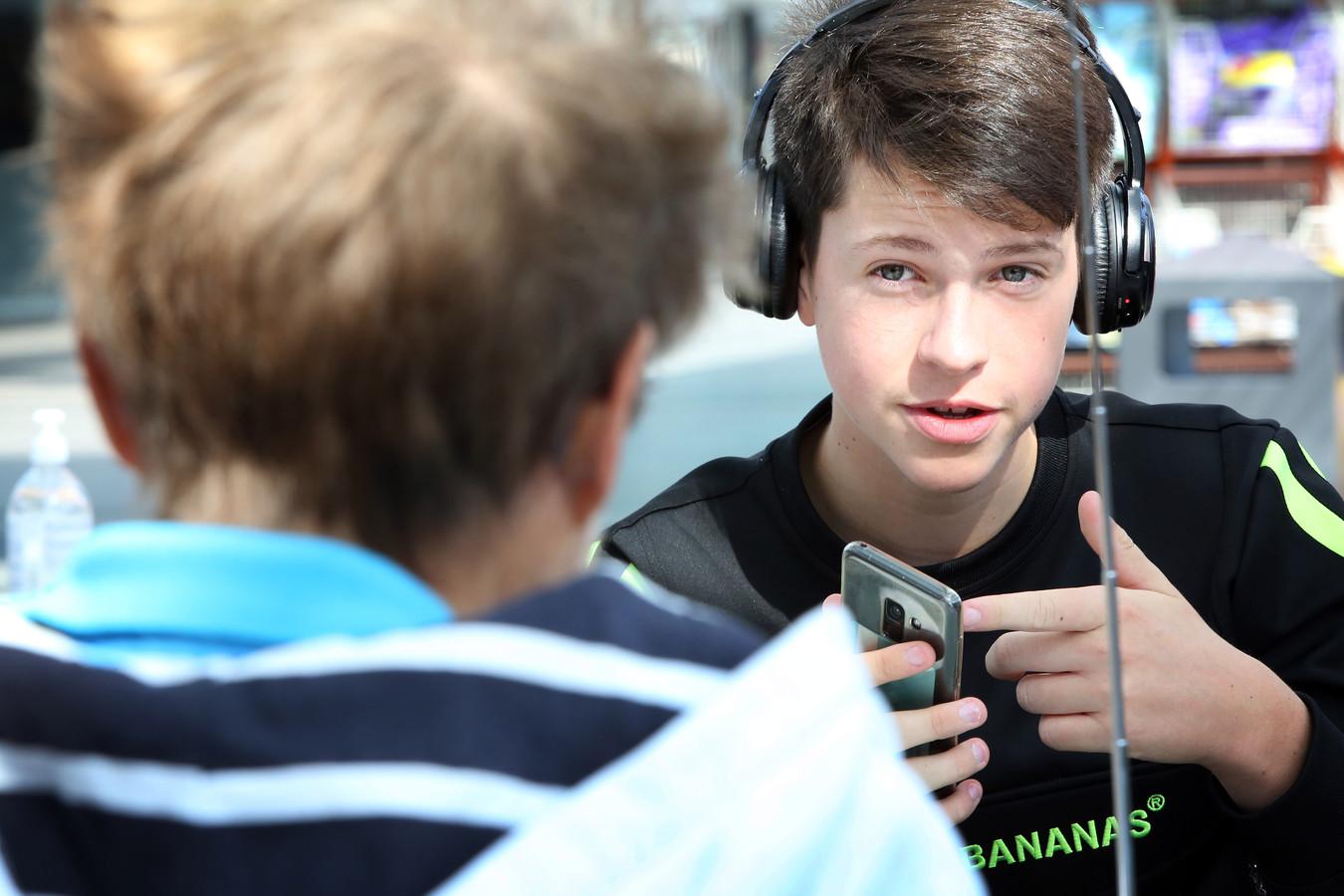 Een jongere is in gesprek met iemand met een gehoorbeperking.