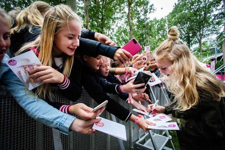 Nina Schotpoort (13 jaar, 133 duizend volgers) deelt handtekeningen uit op het Tina Festival. Beeld ANP