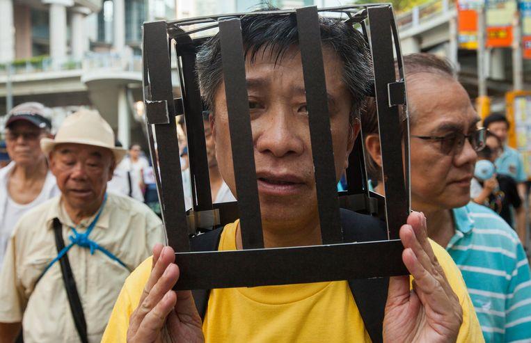 Een demonstrant draagt een kooi op zijn hoofd als protest tegen de  tegen de celstraffen voor activisten Joshua Wong, Nathan Law en Alex Chow. De drie werden vorige week wegens hun leidende rol in de massabetogingen in 2014 veroordeeld tot gevangenisstraffen tussen de zes en acht maanden. Beeld EPA
