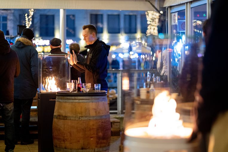 Een bezoeker warmt zijn handen in de Winter Lounge