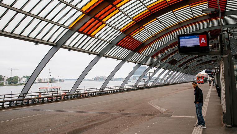 Een reiziger op het Centraal Station wacht tevergeefs op de streekbus. Beeld Marc Driessen