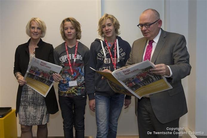 Ian en Vince van der Pal presenteren de eerste kranten aan burgemeester Arco Hofland van Rijssen-Holten en loco-burgemeester Anja van den Dolder van Hellendoorn.