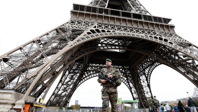 Een soldaat patrouilleert op 14 november 2015 bij de Eiffeltoren in Parijs, een dag na de aanslagen. Beeld epa
