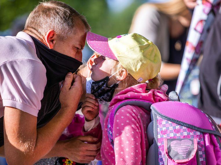 In de Duitse deelstaat Mecklenburg-Vorpommern zijn de scholen deze week weer open gegaan: hier neemt een vader afscheid van zijn dochter op het schoolplein van de Lankow-basisschool in Schwerin. Beeld Jens Büttner/dpa-Zentralbild/dp