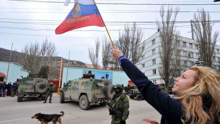 Een vrouw zwaait met de Russische vlag terwijl gewapende mannen de basis van Oekraïnse grenswacht blokkeren. Beeld afp