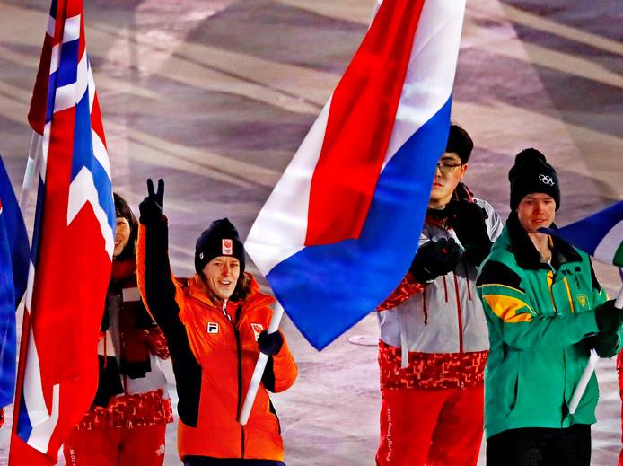Vlaggendraagster Ireen Wüst zwaait naar haar ploeggenoten, die net Olympisch stadion binnenwandelen bij de sluitingsceremonie.
