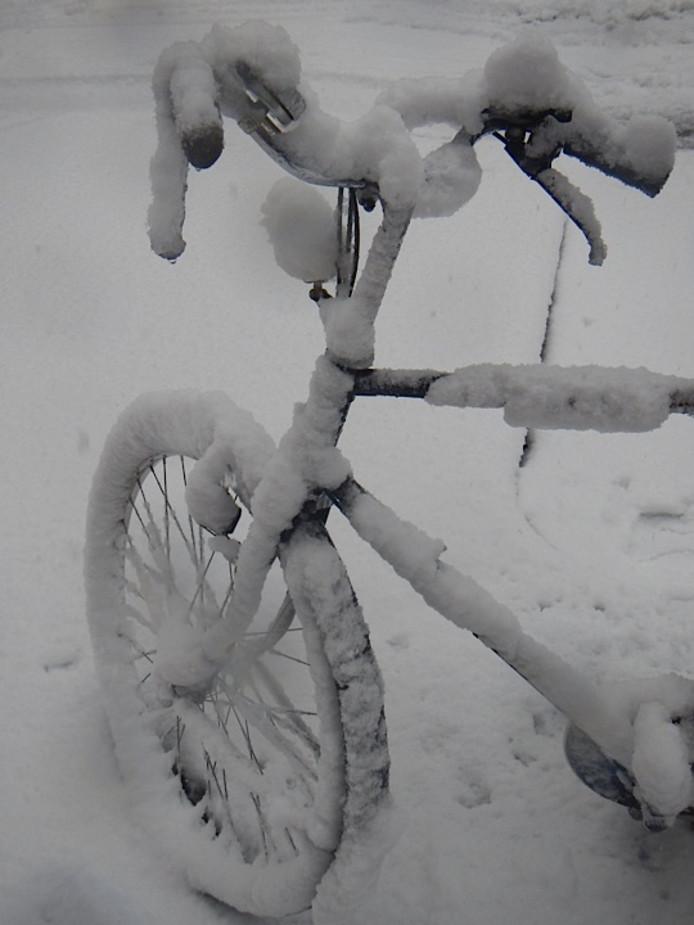 Fiets bedolven onder sneeuw