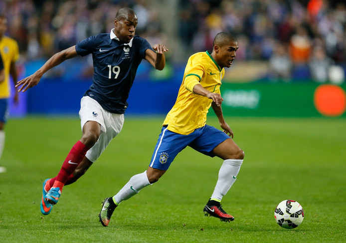 Geoffrey Kondogbia achtervolgt Douglas Costa tijdens de vriendschappelijke interland tussen Frankrijk en Brazilië op 26 maart 2015 in het Stade de France.