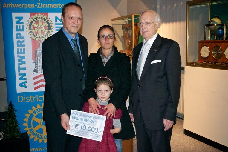 Zoltan Horvath en Jos d'Haens overhandigen Audrey en haar moeder de cheque van 10.000 euro.