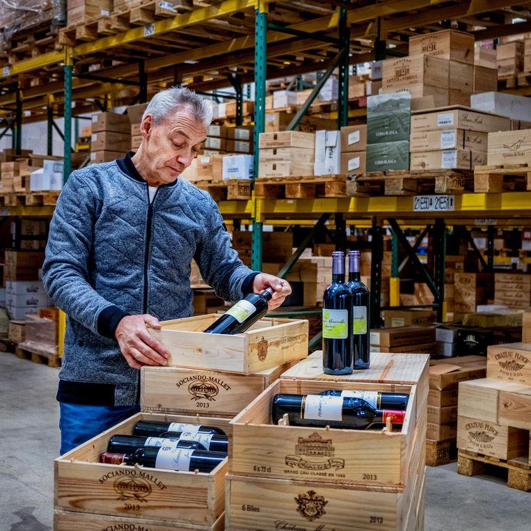 In het magazijn van wijnkoperij Okhuysen worden kistjes wijn gevuld als geschenkverpakking. Beeld Raymon Rutting
