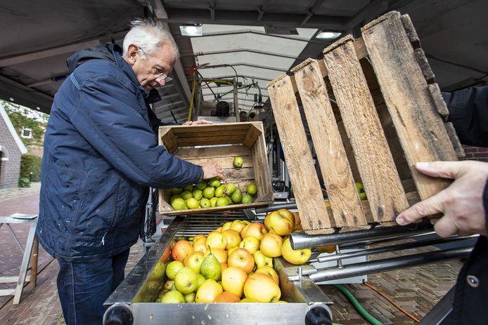 De sap-pers staat naast Bie Winkels. Wim Beskers schudt de appels erin. Veel dorstig publiek is er dit jaar uiteraard niet.